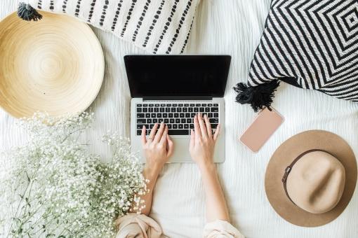 femme travaillant sur son ordinateur portable sur son lit entourés d'objets décoratifs chapeaux, fleurs, smartphone, coussins