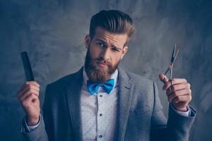 homme barbu en costard gris et noeud bleu tenant dans ses mains un peigne et un ciseau