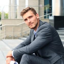 home en costume gris qui pose sur des escaliers